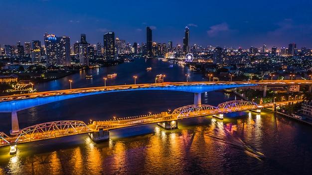 Widok z lotu ptaka bangkok miasta linia horyzontu i drapacz chmur przy nocą z biznesowym budynkiem w bangkok śródmieściu, chao phraya rzeka, bangkok, tajlandia.