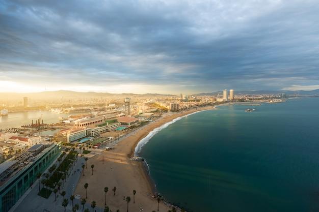 Widok z lotu ptaka barcelona plaża podczas zmierzchu wzdłuż nadmorski w barcelona, hiszpania. śródziemnomorski