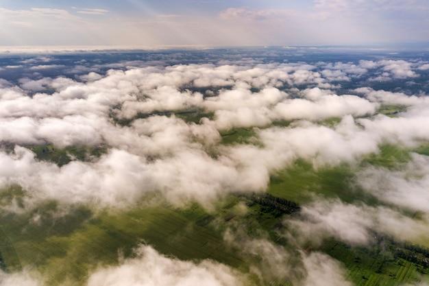 Widok z lotu ptaka białe chmury nad miasteczkiem lub wioską z rzędami budynków i krętymi ulicami między zielonymi polami w lecie. krajobraz wiejski z góry.