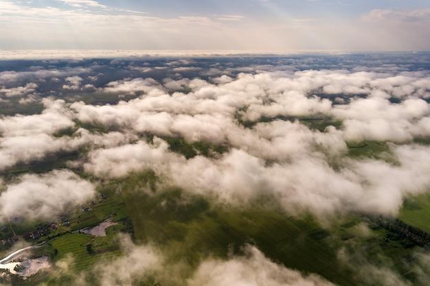 Widok z lotu ptaka białe chmury nad miasteczkiem lub wioską z rzędami budynków i krętymi ulicami między zielonymi polami w lecie. krajobraz wsi z góry.