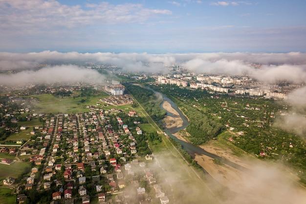 Widok z lotu ptaka białe chmury nad miastem lub wioską z rzędami budynków i krętymi ulicami między zielonymi polami w lecie. krajobraz wsi z góry.