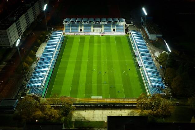 Widok z lotu ptaka boisko do piłki nożnej lub boisko do piłki nożnej podczas gdy atlety lub gracze trenują w nocy pod jasnymi światłami stadionu, praga 15.11.2019