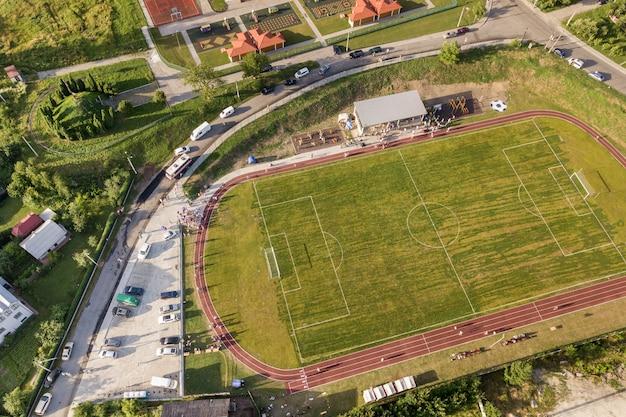 Widok z lotu ptaka boisko do piłki nożnej na stadium zakrywającym zieloną trawą w wiejskim obszarze miasta.