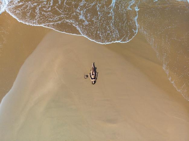 Widok z lotu ptaka brunetki kobiety opalającej się na piasku w pobliżu morza. ma na sobie czarne bikini. ona jest sama.