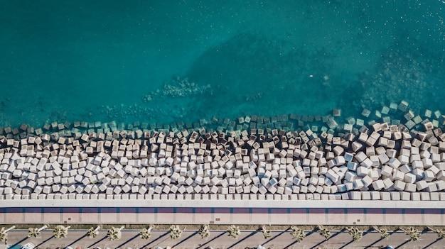 Widok z lotu ptaka cementowi sześcianów bloki ochrania brzeg od fala w porcie malaga, hiszpania.