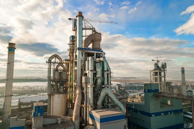 Widok z lotu ptaka cementowni o wysokiej konstrukcji fabrycznej i żurawia wieżowego w obszarze produkcji przemysłowej o zachodzie słońca.
