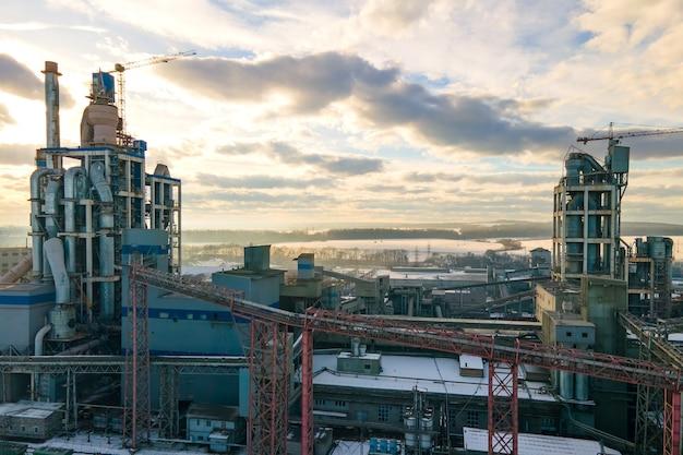Widok z lotu ptaka cementowni o wysokiej konstrukcji fabryki i żurawia wieżowego w obszarze produkcji przemysłowej o zachodzie słońca.