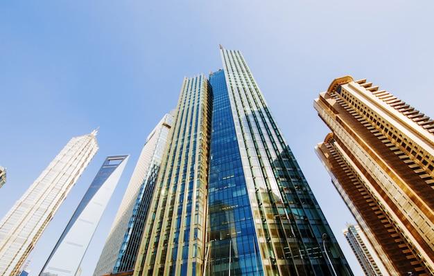 Widok z lotu ptaka centralnej dzielnicy biznesowej w szanghaju. wysokie budynki biurowe i drapacze chmur ze szklaną powierzchnią. drogi miejskie z wieloma pasami ruchu i zielony park miejski. szanghai chiny
