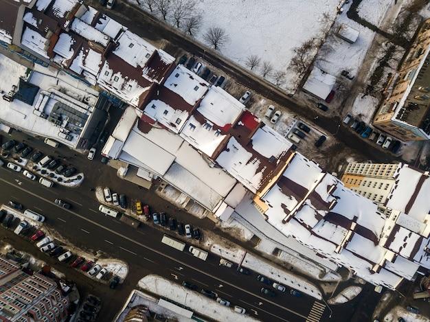 Widok z lotu ptaka czarno-biały zimowy widok z góry nowoczesne miasto z wysokimi budynkami, zaparkowane i jadące samochody wzdłuż ulic z oznakowaniem dróg. gród miejski, widok z góry.
