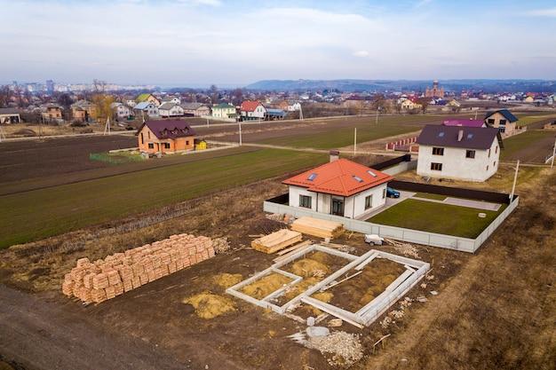 Widok z lotu ptaka dachu nowego domu z oknami poddasza i placem budowy, fundamentem przyszłego domu, stosami cegieł i budową drewnianych bali do budowy.