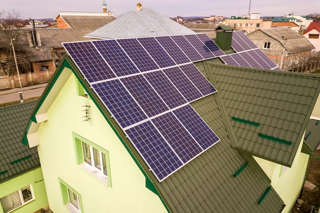 Widok z lotu ptaka domku z niebieskim błyszczącym systemem fotowoltaicznych paneli słonecznych na dachu. odnawialna produkcja ekologicznej zielonej energii.