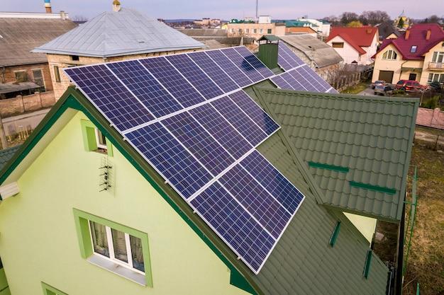 Widok z lotu ptaka domku z niebieskim błyszczącym systemem fotowoltaicznych paneli słonecznych na dachu.