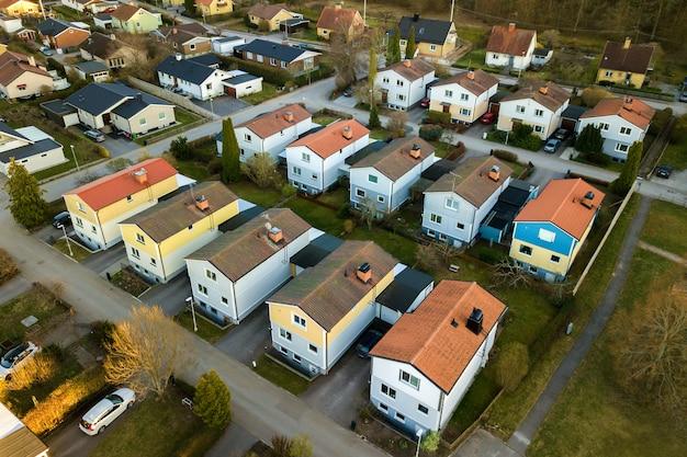 Widok z lotu ptaka domów mieszkalnych z czerwonymi dachami i ulic z zaparkowanymi samochodami na obszarach wiejskich.