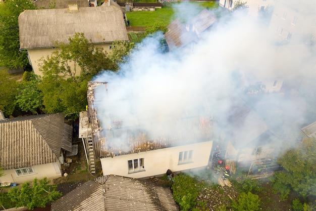 Widok z lotu ptaka domu w ogniu z pomarańczowymi płomieniami i białym gęstym dymem.