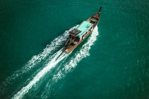Widok z lotu ptaka: drewniana łódź rybacka pływa po morzu i pozostawia fale za sobą
