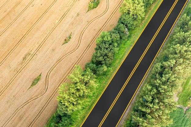 Widok z lotu ptaka drogi między żółtymi polami pszenicy i zielonymi drzewami.