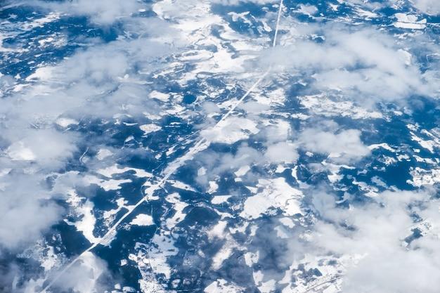 Widok z lotu ptaka drogi ze śniegiem i górą w chmurach