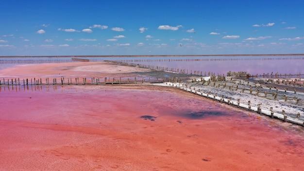 Widok z lotu ptaka drona drewnianych konstrukcji do zbierania soli na różowym jeziorze, genichesk, ukraina. jezioro naturalnie zmienia kolor na różowy z powodu soli i małej artemii skorupiaków w wodzie.