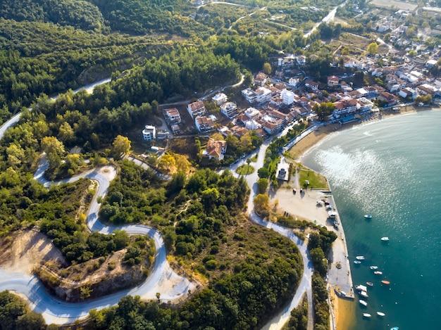 Widok z lotu ptaka drona na błękitne morze i wietrzne górskie drogi w halkidiki w grecji