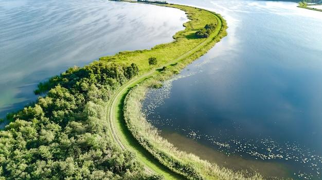 Widok z lotu ptaka drona na ścieżkę na tamie w wodzie polderowej z góry