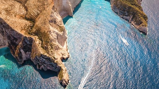 Widok z lotu ptaka drona na wybrzeże morza jońskiego w zakynthos grecja skalisty grzbiet pływające łodzie