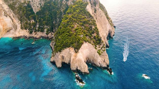 Widok z lotu ptaka drona na wybrzeże morza jońskiego zakynthos grecja skalisty grzbiet zieleni pływająca łódź