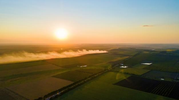 Widok z lotu ptaka drona natury w mołdawii o zachodzie słońca. dym z ogniska, szerokie pola, droga, słońce