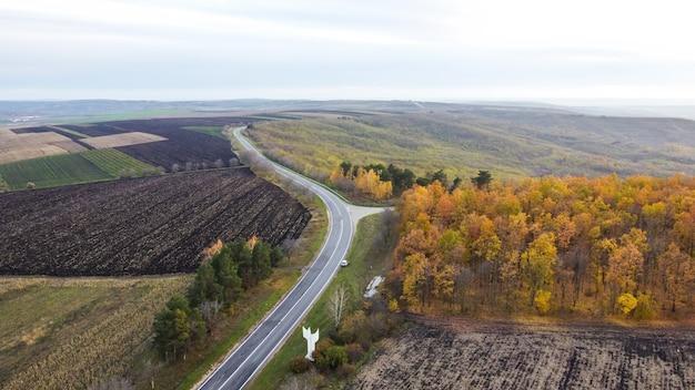 Widok z lotu ptaka drona przyrody w mołdawii, obsiane pola, droga, częściowo pożółkłe drzewa, wzgórza, zachmurzone niebo