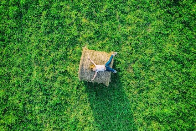 Widok z lotu ptaka drona szczęśliwy uśmiechający się dziewczyna z dżinsami na beli siana i zielonej trawie łące.