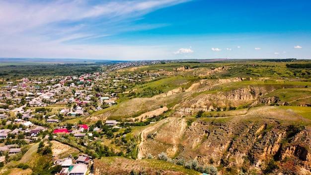 Widok z lotu ptaka drona wsi w mołdawii. budynki mieszkalne, niskie pagórki, zieleń