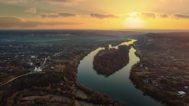 Widok z lotu ptaka drona wsi w mołdawii o zachodzie słońca rzeka starych budynków mieszkalnych kościoła