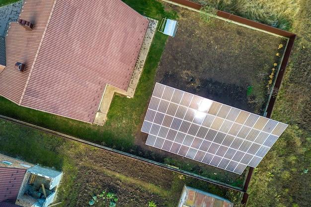Widok z lotu ptaka dużego niebieskiego panelu słonecznego zainstalowanego na konstrukcji naziemnej w pobliżu prywatnego domu.
