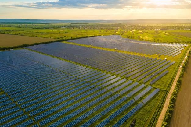 Widok z lotu ptaka dużej zrównoważonej elektrowni z wieloma rzędami paneli fotowoltaicznych