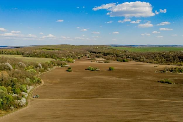 Widok z lotu ptaka duży ciągnik uprawiający suche pole. ciągnik z widokiem z góry na dół, uprawiający ziemię i wysiewający suche pole. ciągnik antenowy tnie bruzdy na polu gospodarstwa do siewu.