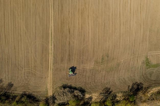 Widok z lotu ptaka duży ciągnik uprawiający suche pole. ciągnik z widokiem z góry na dół, uprawiający ziemię i wysiewający suche pole. ciągnik powietrzny tnie bruzdy na polu farmy do siewu.