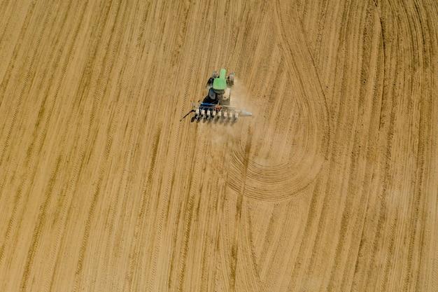 Widok z lotu ptaka duży ciągnik uprawiający suche pole. ciągnik z widokiem z góry na dół, uprawiający ziemię i wysiewający suche pole.