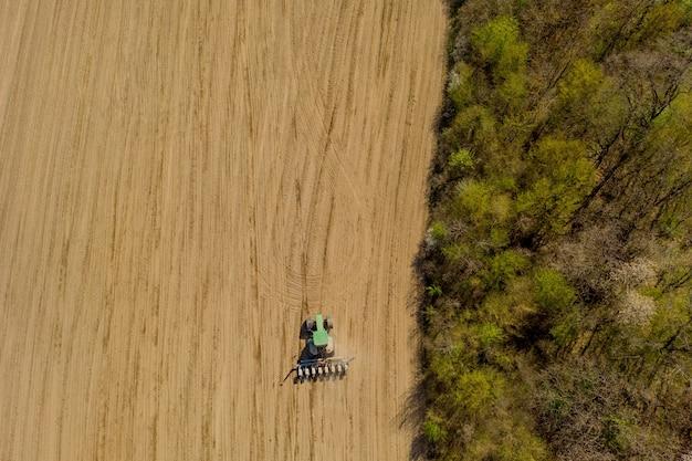 Widok z lotu ptaka duży ciągnik uprawiający suche pole. ciągnik z widokiem z góry na dół uprawiający ziemię i wysiewający suche pole