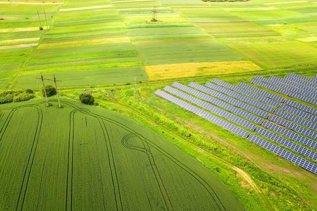 Widok z lotu ptaka elektrowni słonecznej na zielonym polu. panele elektryczne do wytwarzania czystej energii ekologicznej.