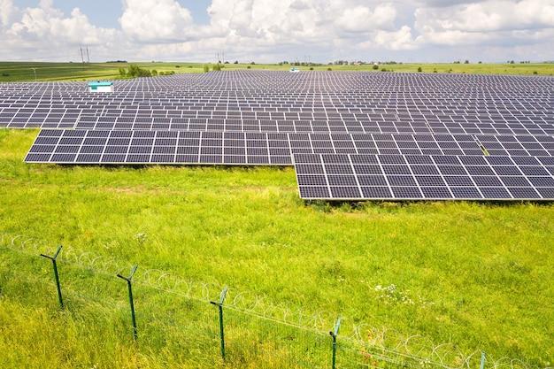 Widok z lotu ptaka elektrowni słonecznej na zielonym polu z ogrodzeniem z drutu ochronnego wokół niego. panele elektryczne do wytwarzania czystej energii ekologicznej.