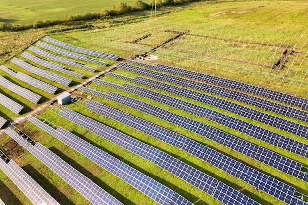 Widok z lotu ptaka elektrowni słonecznej w budowie na zielonym polu. montaż paneli elektrycznych do produkcji czystej energii ekologicznej.
