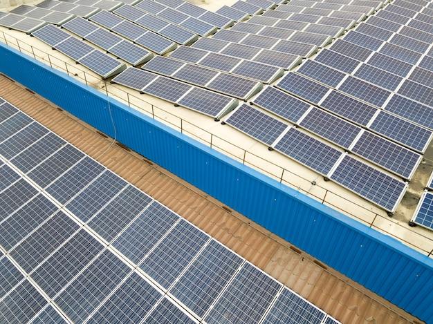 Widok z lotu ptaka elektrowni słonecznej z niebieskimi panelami fotowoltaicznymi zamontowanymi na dachu budynku przemysłowego.