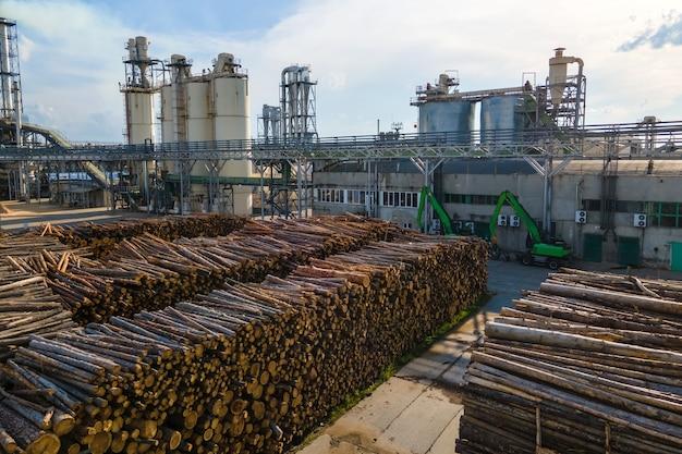 Widok z lotu ptaka fabryki obróbki drewna ze stosami drewna w stoczni produkcyjnej zakładu.