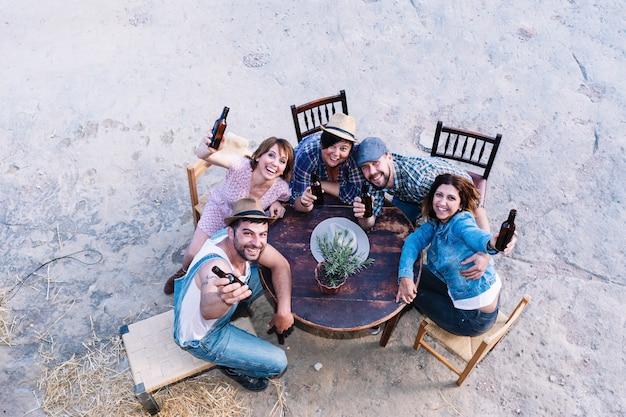 Widok z lotu ptaka grupy przyjaciół siedząc przy stole, trzymając piwa