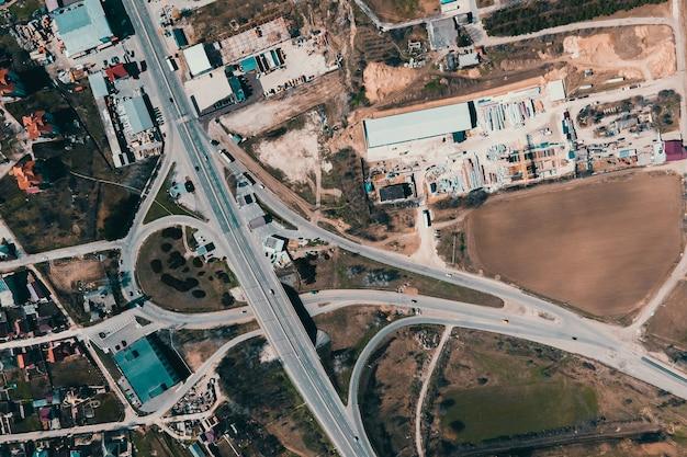 Widok z lotu ptaka infrastruktury obszaru przemysłowego na obrzeżach miasta samochody autostrady budynki słoneczny wiosenny transport i infrastruktura
