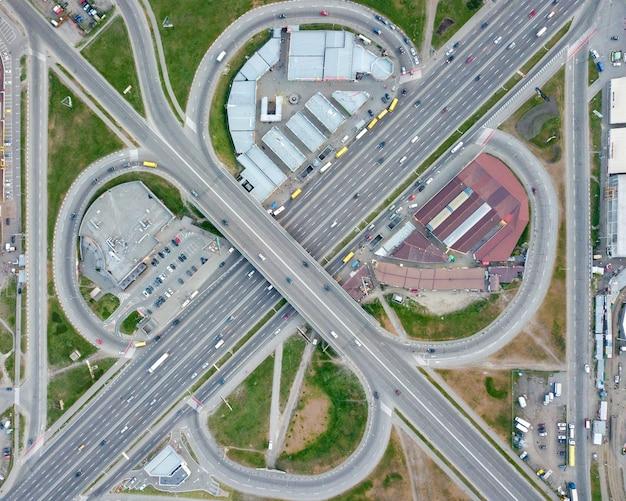 Widok z lotu ptaka kijów, ukraina wiadukt drogowy z samochodami, budynkami i parkingiem z zaparkowanymi samochodami powiat poznyaki. zdjęcie drona