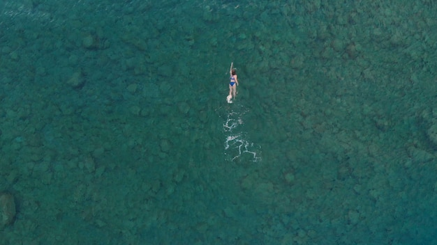 Widok z lotu ptaka: kobieta pływająca na powierzchni błękitnej wody, pływająca w przejrzystym morzu śródziemnomorskim, widok z góry, koncepcja wakacji letnich