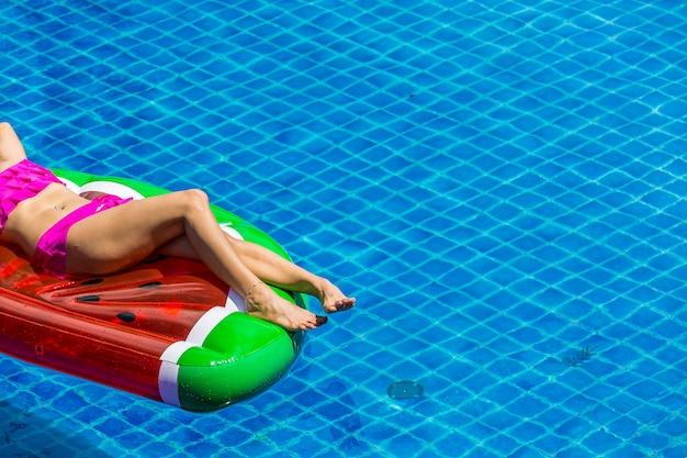 Widok z lotu ptaka kobieta w bikini lying on the beach na spławowej materac w pływackim basenie.