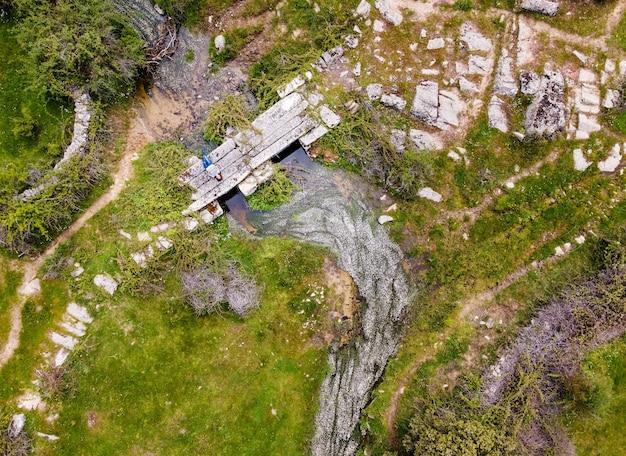Widok z lotu ptaka kobiety leżącej na starym kamiennym moście w zielonym polu