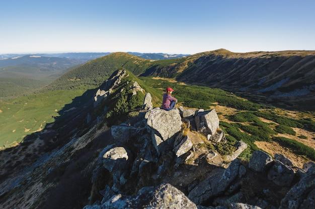 Widok z lotu ptaka kobiety turysty relaksującej się na szczycie góry i cieszącej się koncepcją widoku na dolinę