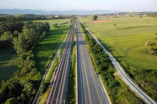 Widok z lotu ptaka, kolej i droga w wiejskim krajobrazie.